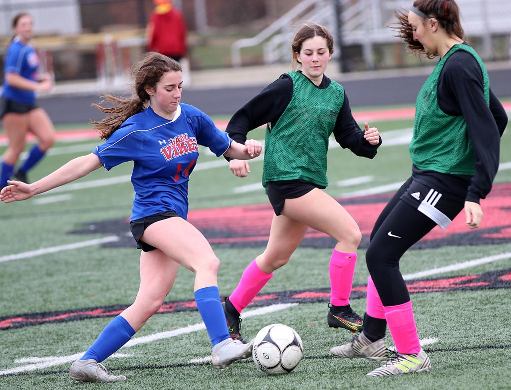 AHSTW senior Julia Kock (14) pushes the ball upfield as Claire Schmitz (right) and Madison Kjergaard defend for HCHS.