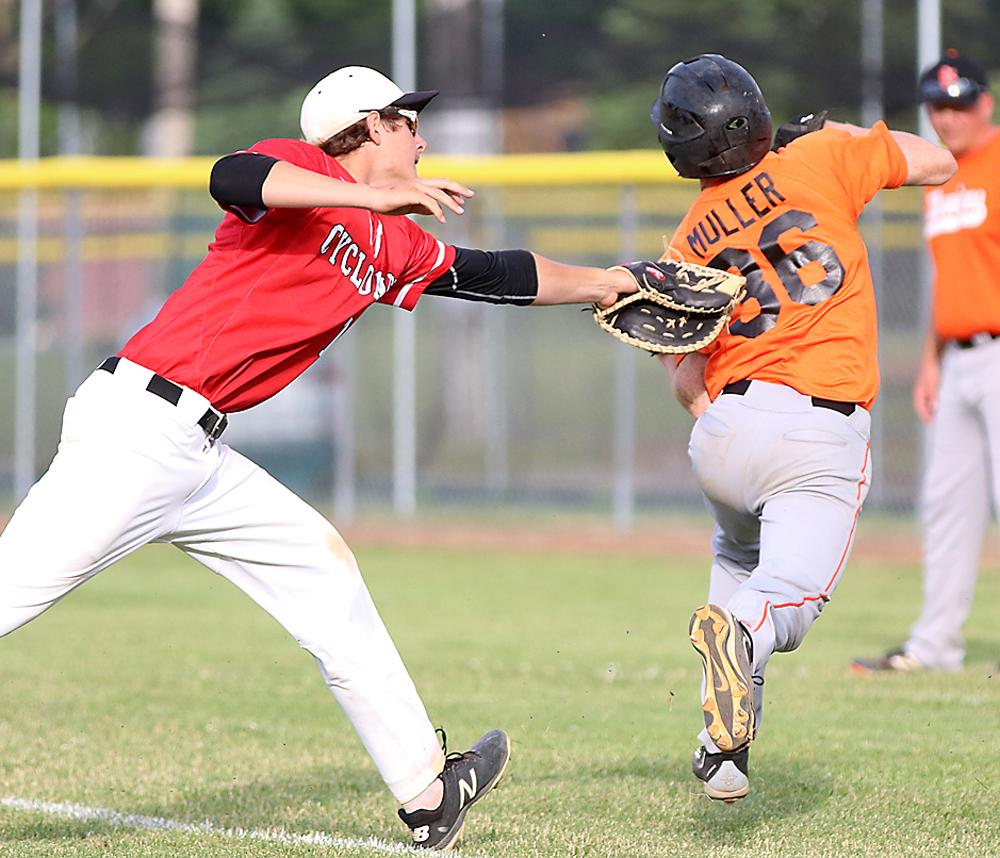 HCHS first baseman Riley Kohles tags out the Warriors' Nick Muller after fielding his sacrifice bunt.