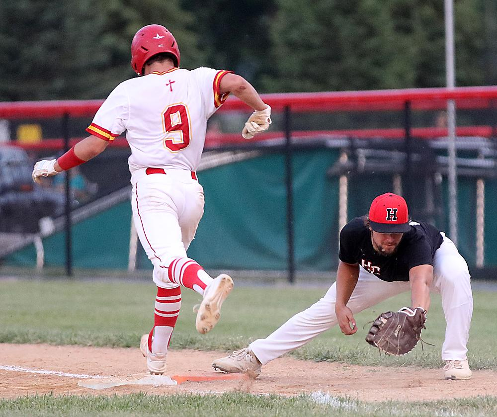 HCHS first baseman Kelby Lasher (right) catches the ball to retire Kuemper's Logan Sibenaller on a dropped third strike.