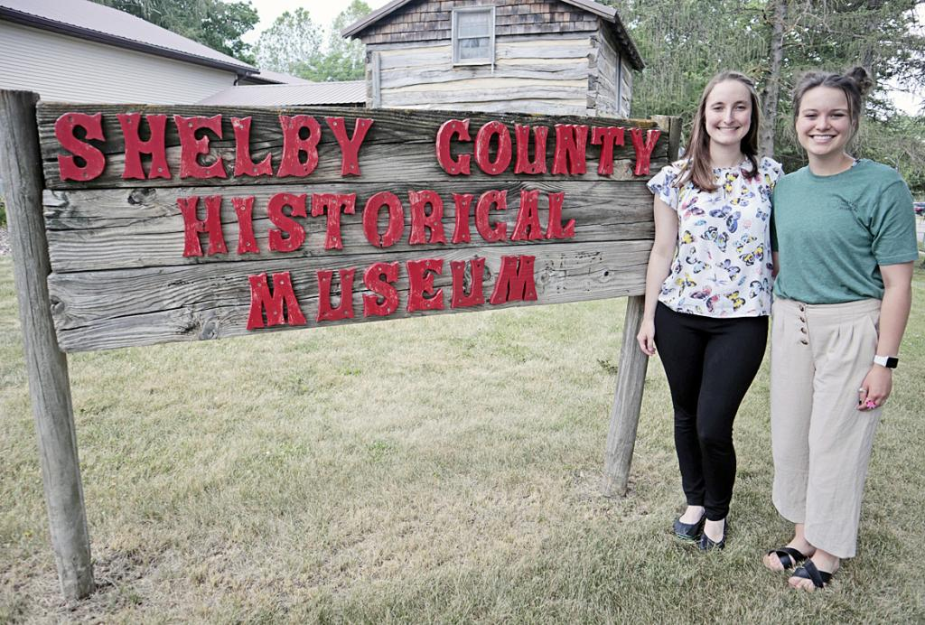 Lauren Jones (right) and Sarah McDonald are the Shelby County Historical Museum's only two employees. The women, who each moved to Harlan within the past few years, are pictured outside of the museum earlier this month.  (Photo by Molly Blanco)