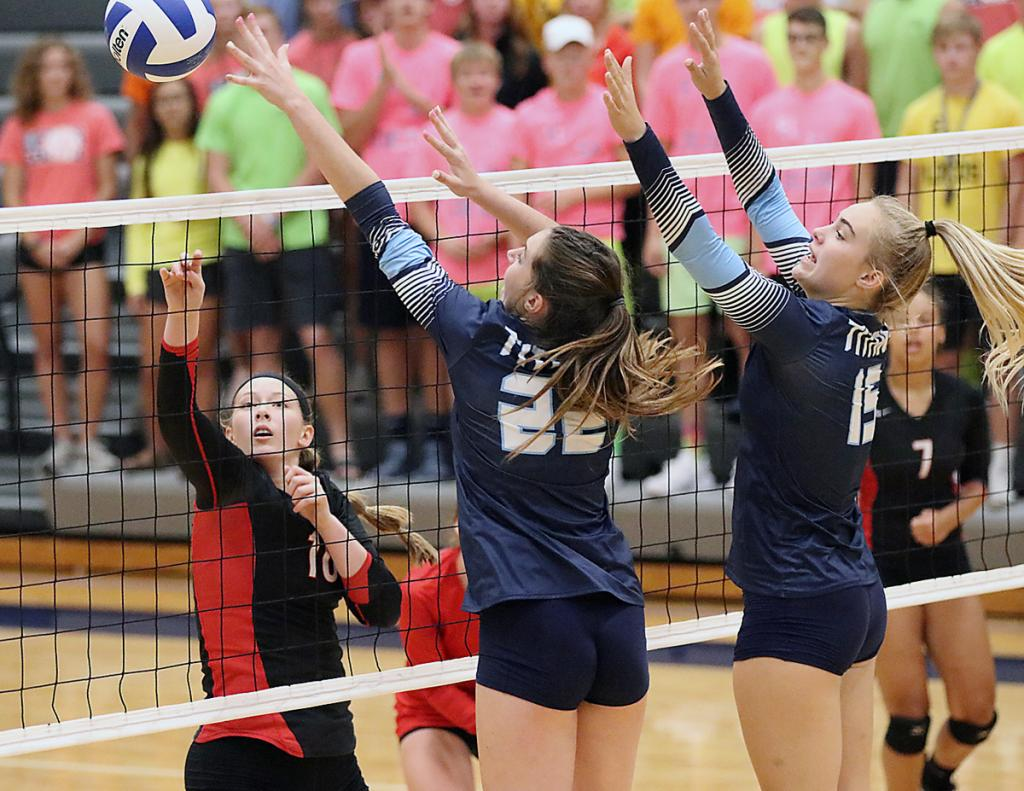 Harlan Community senior Olivia Petersen (left) tips the ball around the block of Lewis Central's Madisyn Havermann (22) and Delaney Esterling during Tuesday's Hawkeye Ten match.