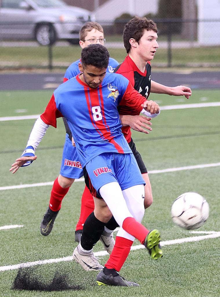 Jay Patel of AHSTW (8) sends the ball upfield as he is bumped by HCHS junior Ashton Lyon.