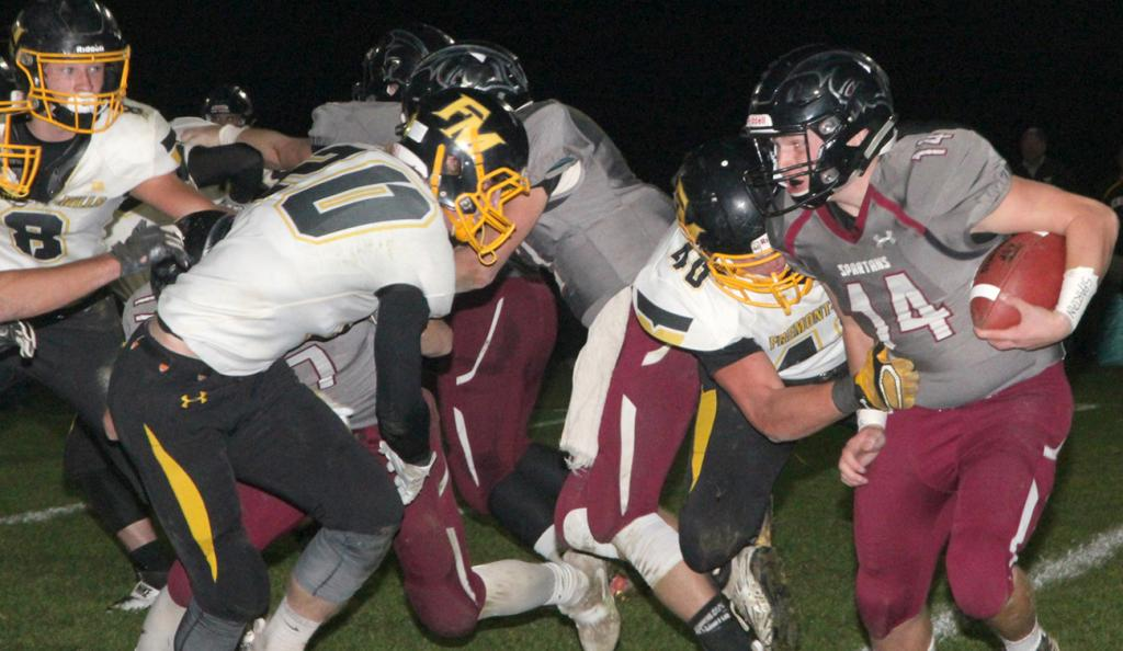 Exira-EHK quarterback Josh Pettepier (right) faces down the rush of Fremont-Mills tacklers Connor Alley (40) and Austin Gartner (20) during last week's 61-20 playoff loss to the Knights. (Photos by Kim Wegener)