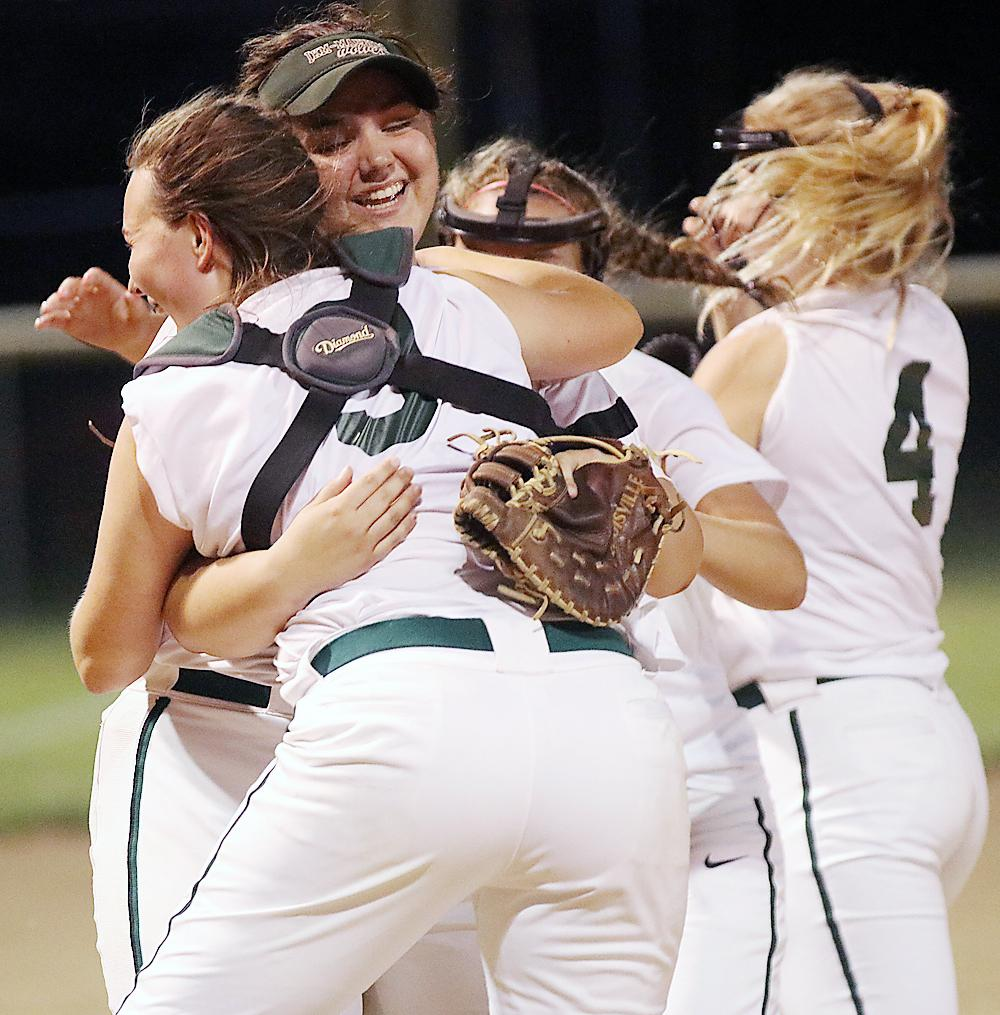 IKM-Manning first baseman Grace Youngren (center) hugs catcher Zoey Melton after the Wolves beat Underwood 7-6 in the first round of the WIC Softball Tournament Tuesday night. Youngren hit a two-run homer in the first inning and later caught the final out.