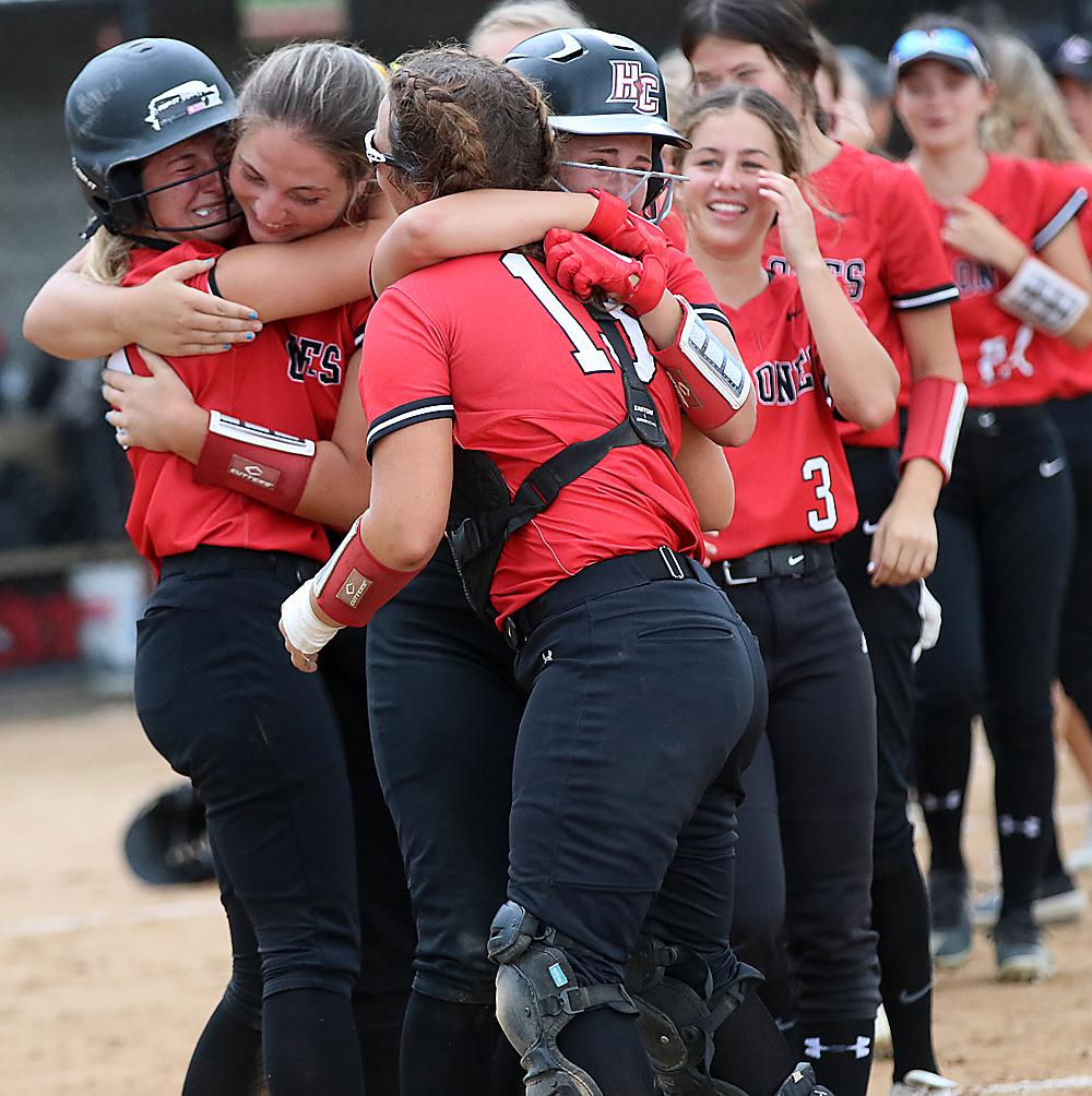 HCHS players celebrate the walk-off victory. Kennedy Kjergaard (far left), who started the seventh-inning rally with a triple, hugs Emily Brouse while catcher Madison Schumacher is hugged by Kate Heithoff.