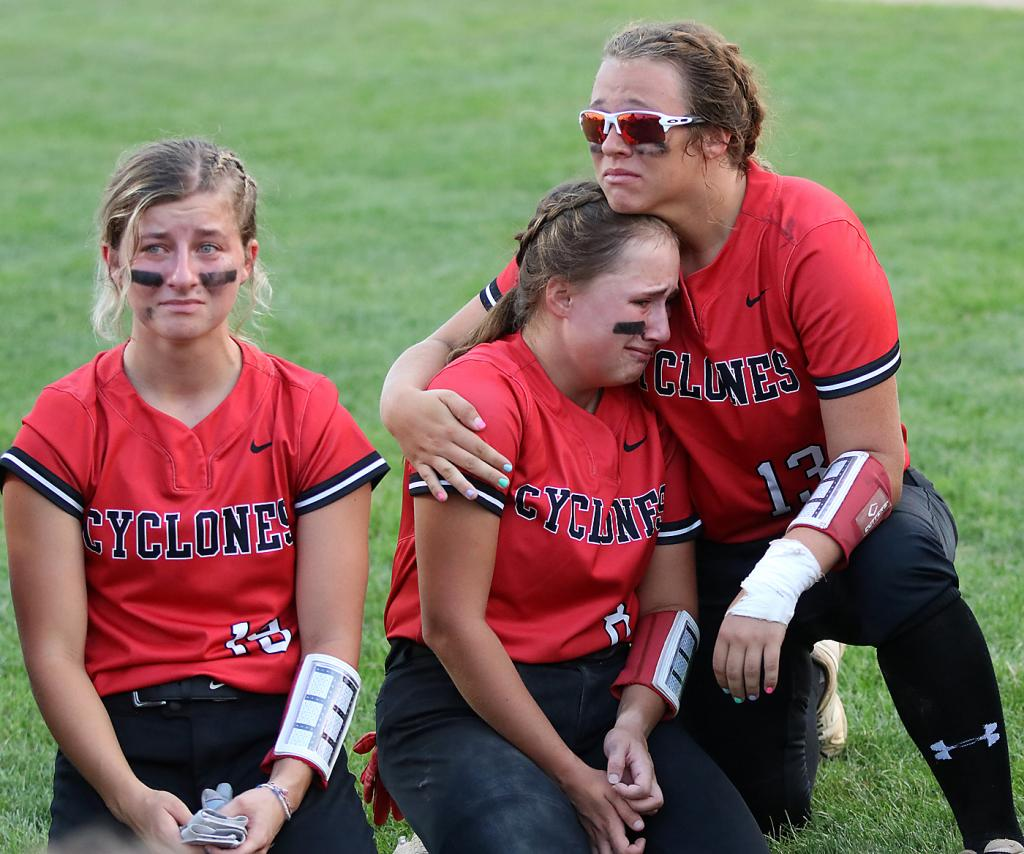 Harlan Community senior Madison Schumacher (right) puts her arm around junior Kate Heithoff as senior Kennedy Kjergaard also reacts following the Cyclones' 10-0, five-inning loss to Winterset in Tuesday's Class 4A regional final.