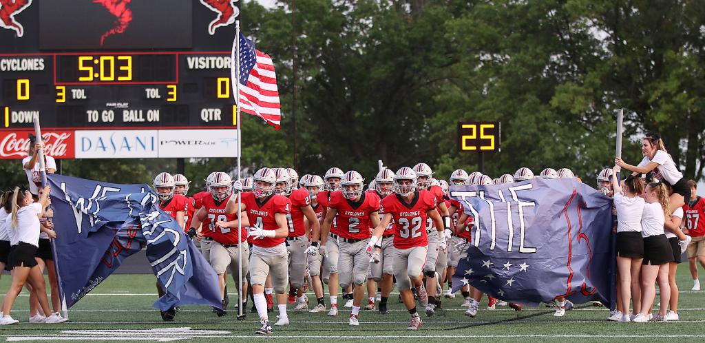 """HCHS senior Ashton Lyon carries the American flag as he leads the Cyclone football team on the field for Friday night's game against Sergeant Bluff-Luton. On the eve of the 20th anniversary of 9/11, there was a patriotic feel at Merrill Field. The HCHS cheerleaders' pregame banner stated """"We Honor The Fallen: 13"""" in reference to the 13 U.S. service members killed in Afghanistan last month."""