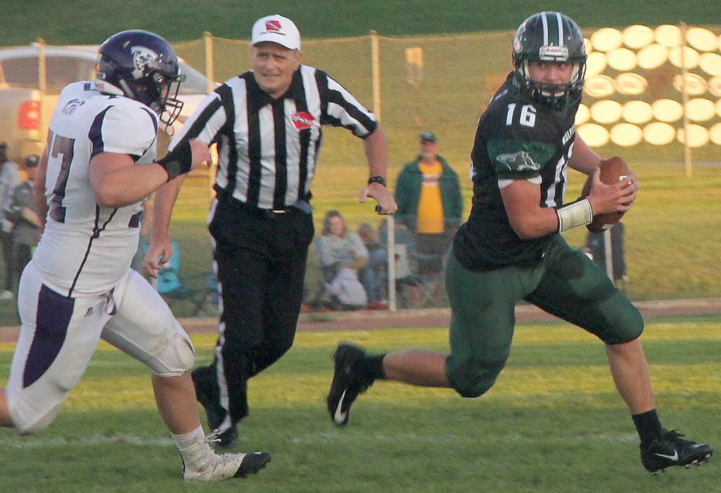 IKM-M quarterback Kyler Rasmussen eludes the pass rush of a Titan lineman. (Photos by Kim Wegener)