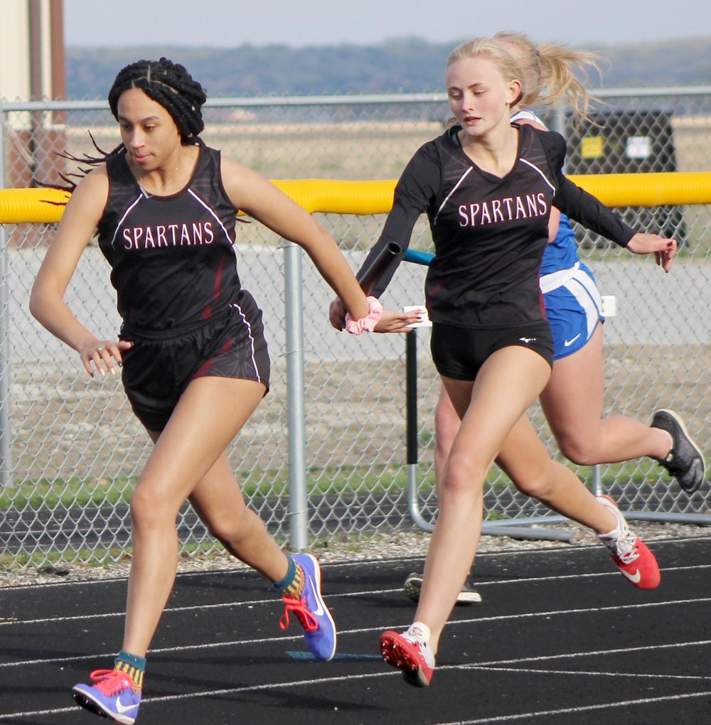 Makaela Riley (right) and Selena Nichols make the first exchange in Exira-EHK's second-place distance medley relay, which also included Camryn Paulsen and Shelbi Wilson.
