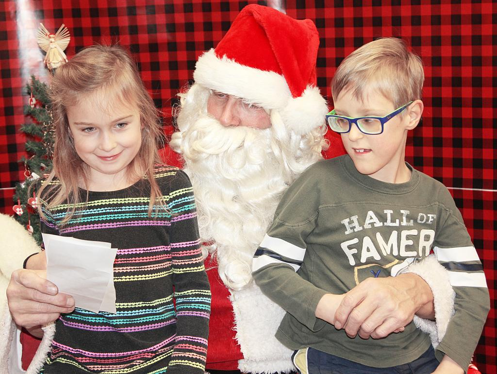ELK HORN -- Mary Eldal and her brother, Alex Eldal, listen as Santa Claus reads through their Christmas wish list.  (Photo by Kim Wegener)