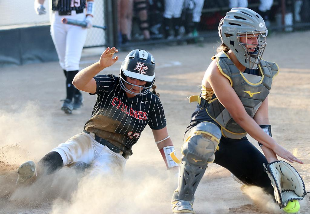HCHS senior Madison Schumacher scores a ninth-inning run during Tuesday's home loss to Atlantic as Trojan catcher Alyssa Derby fields a throw from the outfield.