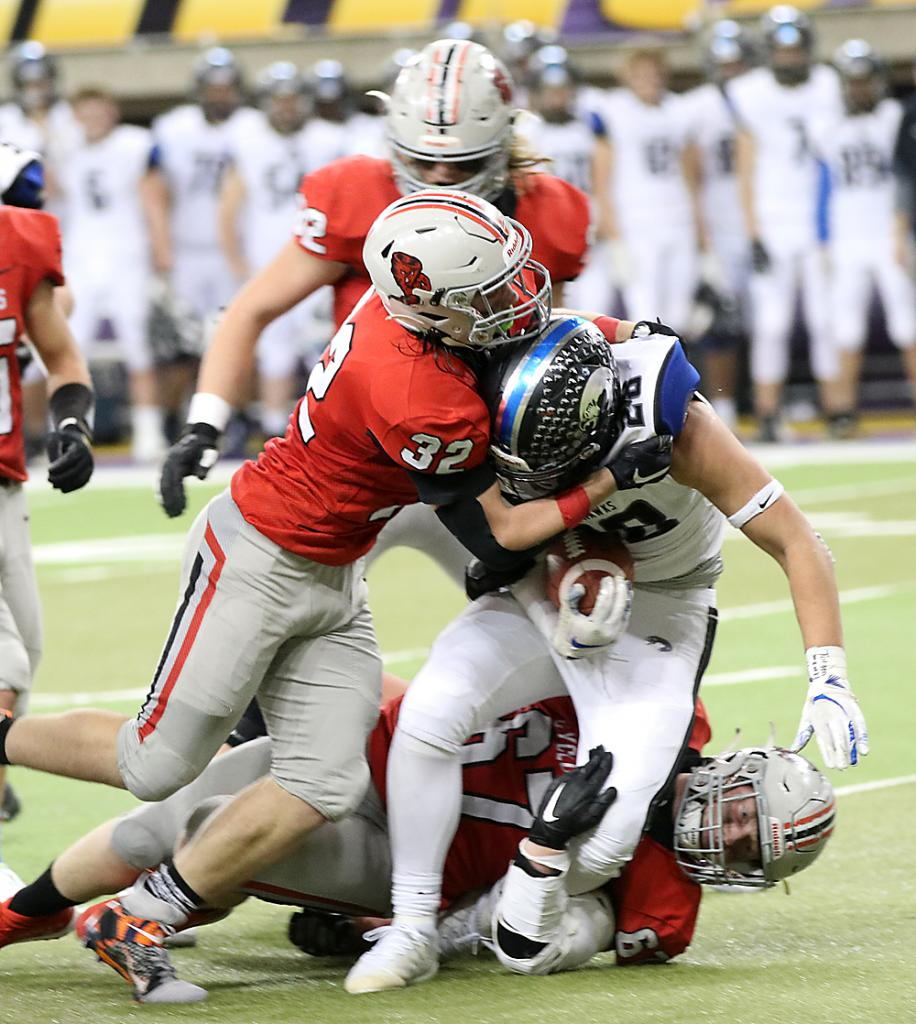 Nighthawk ball carrier Cade Fisher is tackled in the backfield by HCHS linebacker Lucas Stanley (32) and defensive tackle Jesse Schwery.