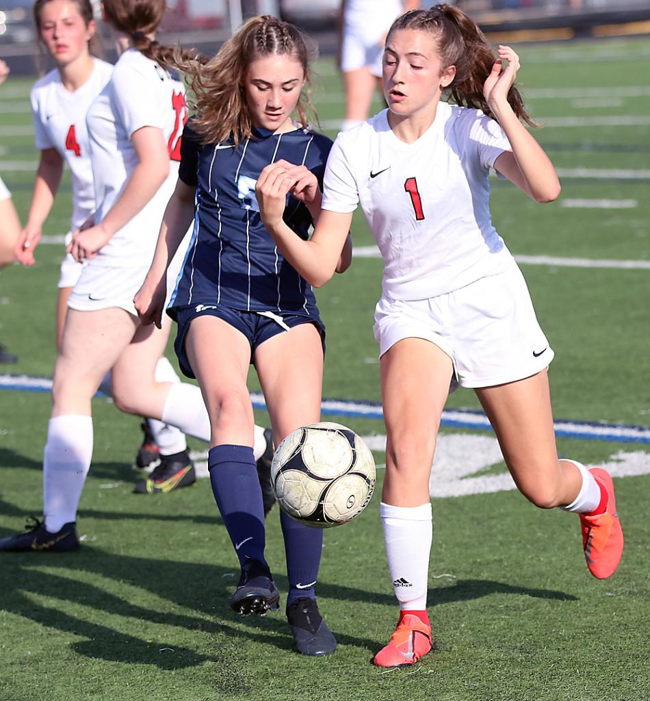 HCHS freshman Taylor Bieker (1) competes for the ball with Lewis Central's Isabel McNeal.