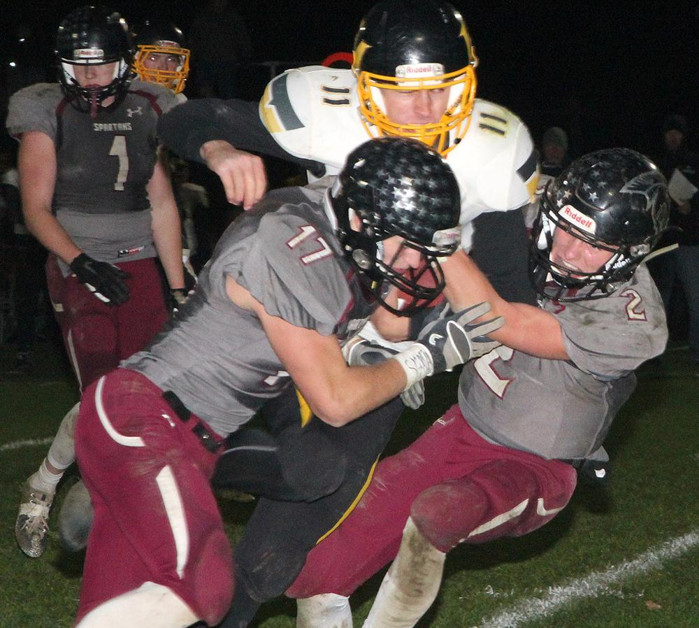 Fremont-Mills quarterback Mason Vanatta (11) is tackled by Spartan seniors Ian Leader (17) and Cole Burmeister (2).