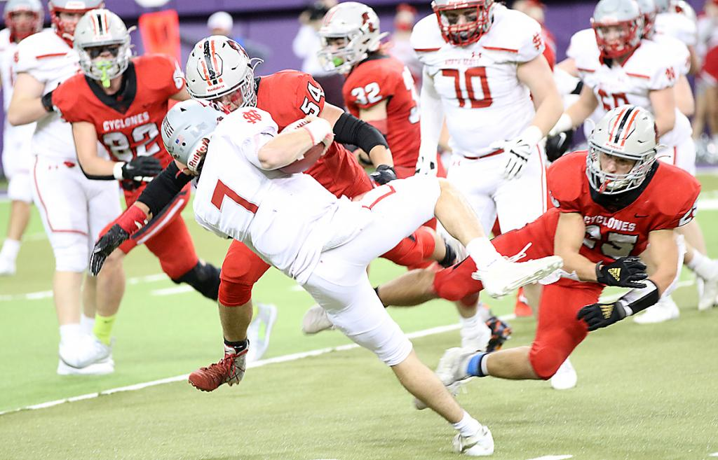 North Scott quarterback Carter Markham (7) is tripped up by HCHS senior Brenden Bartley (right) as senior Chandler Leinen (54) looks to finish off the tackle.