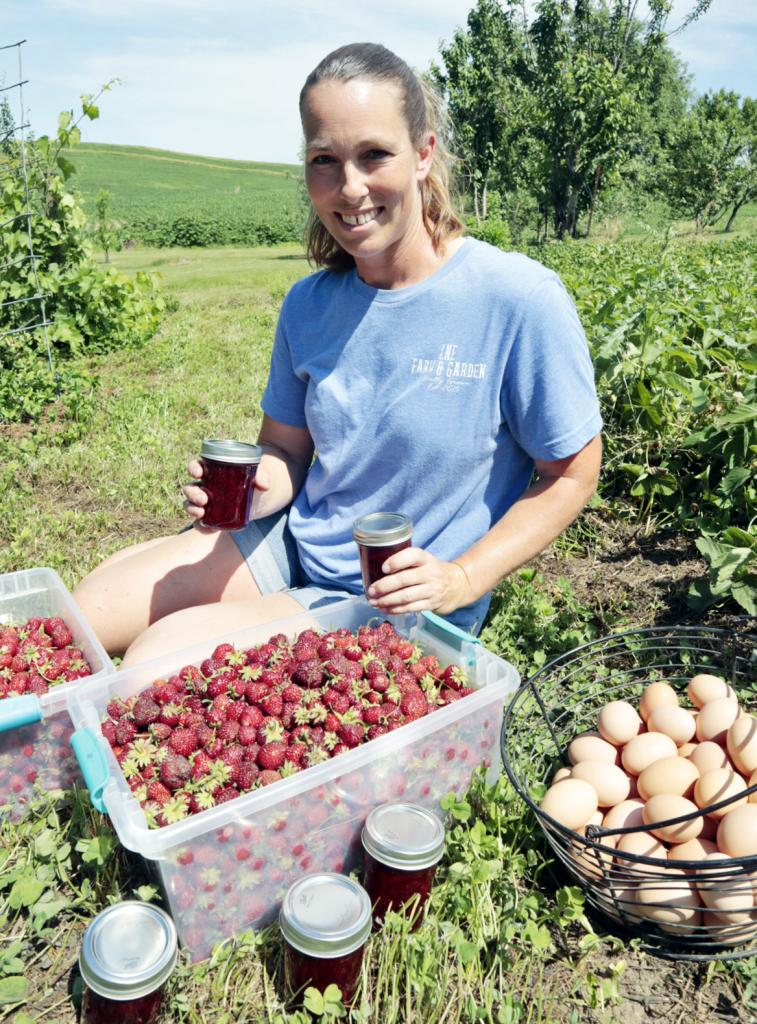 Lori Tarney poses with some of her freshly picked strawberries, homemade jam and farm eggs in her strawberry patch near Avoca Monday, June 14. Tarney's business, LNE Farm and Garden, participates in the Shelby County Farmers Market every year.