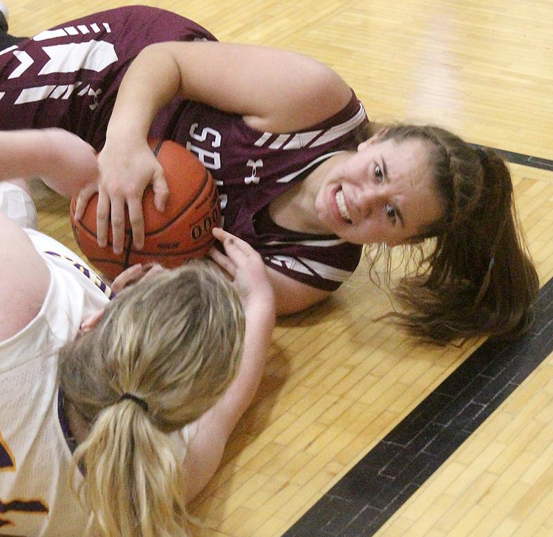 Exira-EHK sophomore Tatum Grubbs (right) fights for a loose ball against Logan-Magnolia. (Photo courtesy of Matt Gengler, Missouri Valley Times)