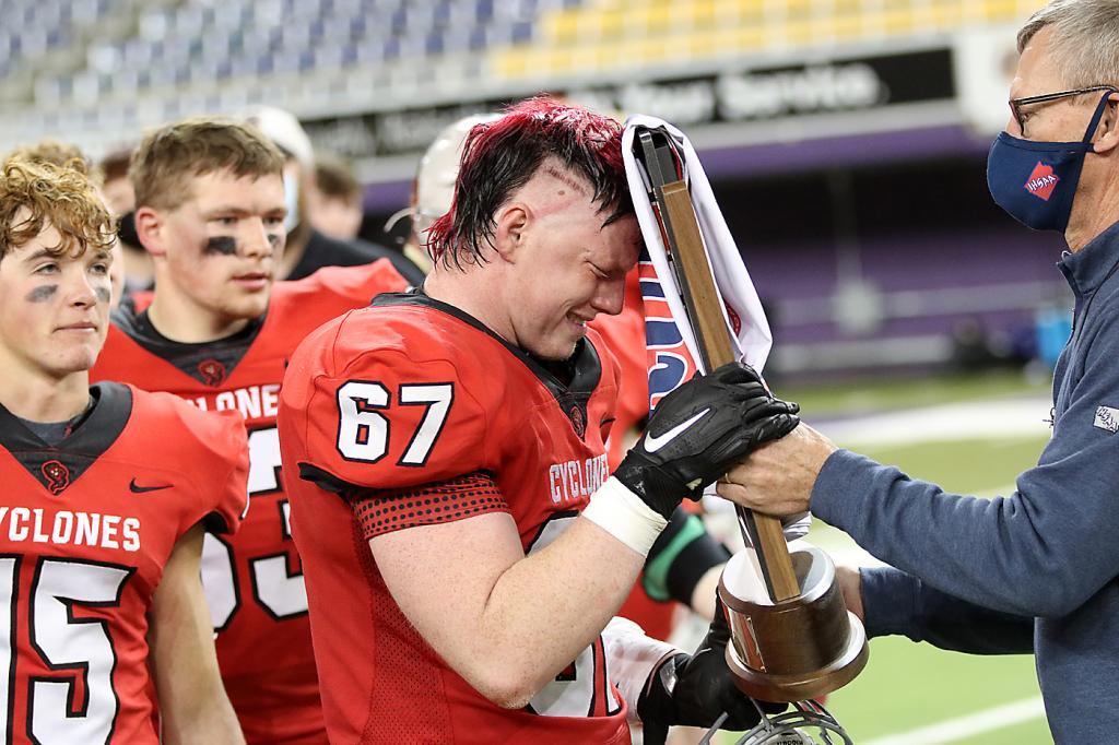 Cyclone senior Jesse Schwery accepts the trophy from an IHSAA official.