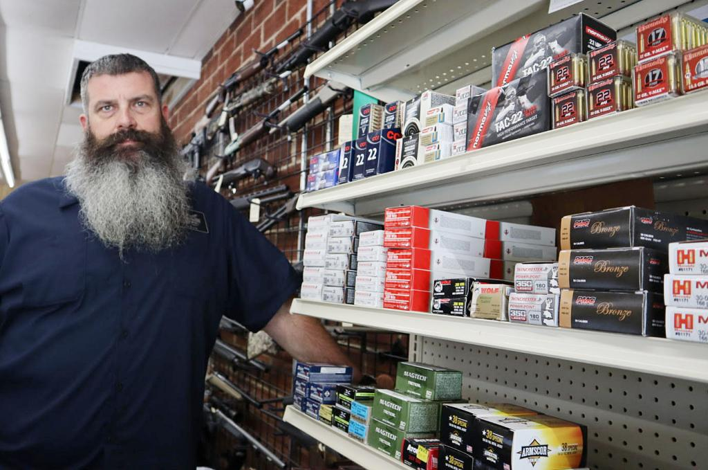 """Thunder Guns West owner Vernon Schwarte stands next to the ammunition shelf at his store after a recent restock. The shelf carries the store's entire supply of ammunition, and many varieties are out of stock or in short supply. """"Normally, this entire shelf and another one would be full,"""" Schwarte said. """"There are dozens and dozens of rounds of ammo that we cannot get in stock."""""""