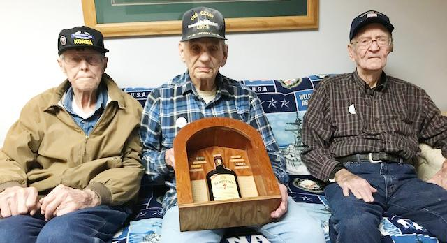 Alvin Heller, middle, is the last World War II veteran from the Portsmouth American Legion.  He was presented this bottle of whiskey recently by the Legion post.  Heller is pictured with fellow veterans Leo Hawn (left), Earling, a Korean War veteran, and Bob Kuster, Persia, Korean War veteran.