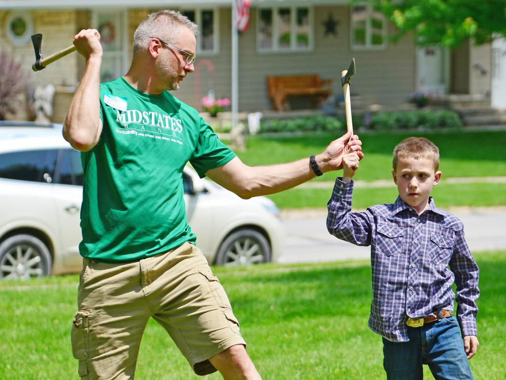 Ryan Brodersen (left) shows a youngster how to throw an axe and hit a target.