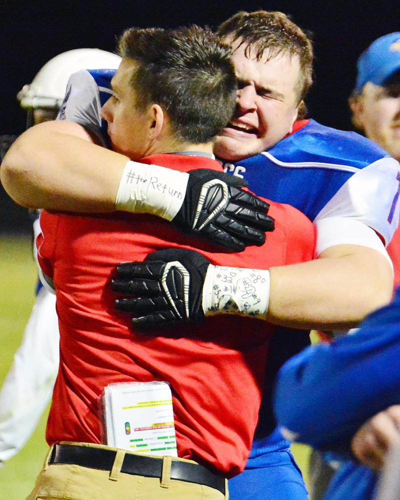 WELCOME BACK -- AHSTW coach Davis Pattee gets an emotional hug from junior Brady Canada following Friday's playoff victory. Canada saw his first action of the year after recovering from preseason knee surgery.