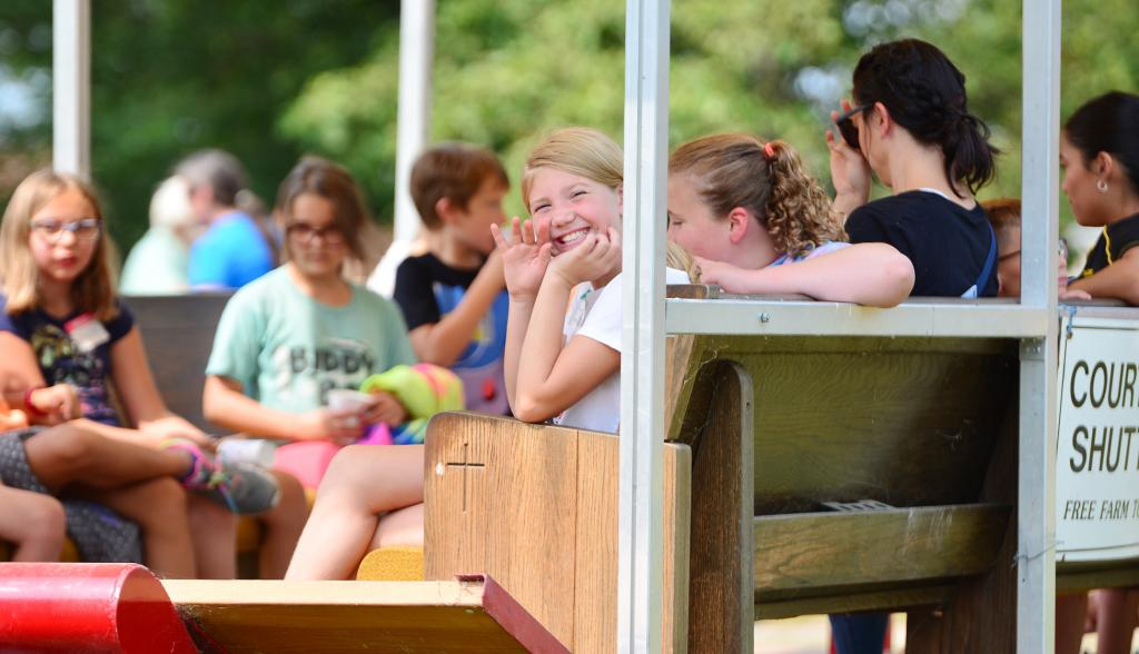 Smile and a wave from students on the courtesy shuttle traveling throughout the farm.