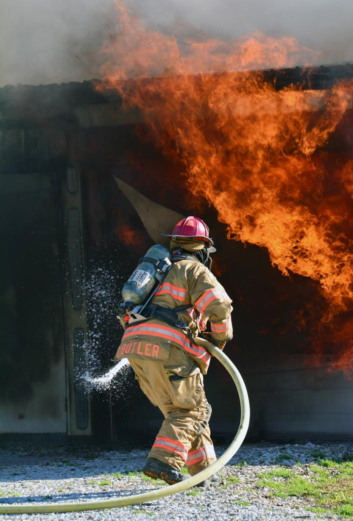 Harlan Firefighter Chad Butler races to douse the flames with water as the high winds whip up the fire inside the garage Thursday.  Firefighters were on scene for about two hours making sure the hot spots did not re-kindle.  The garage was listed as a total loss.