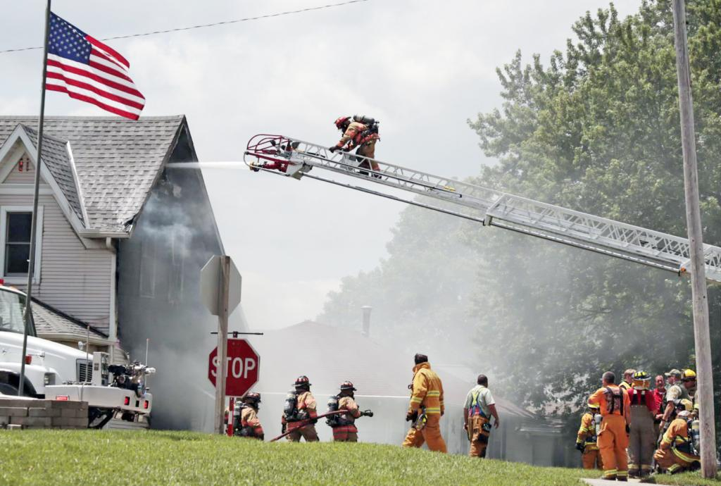 Firefighters shoot water into the home along Madison Ave. in Elk Horn Tuesday to keep the fire under control.  An individual inside is alleged to have started the fire.