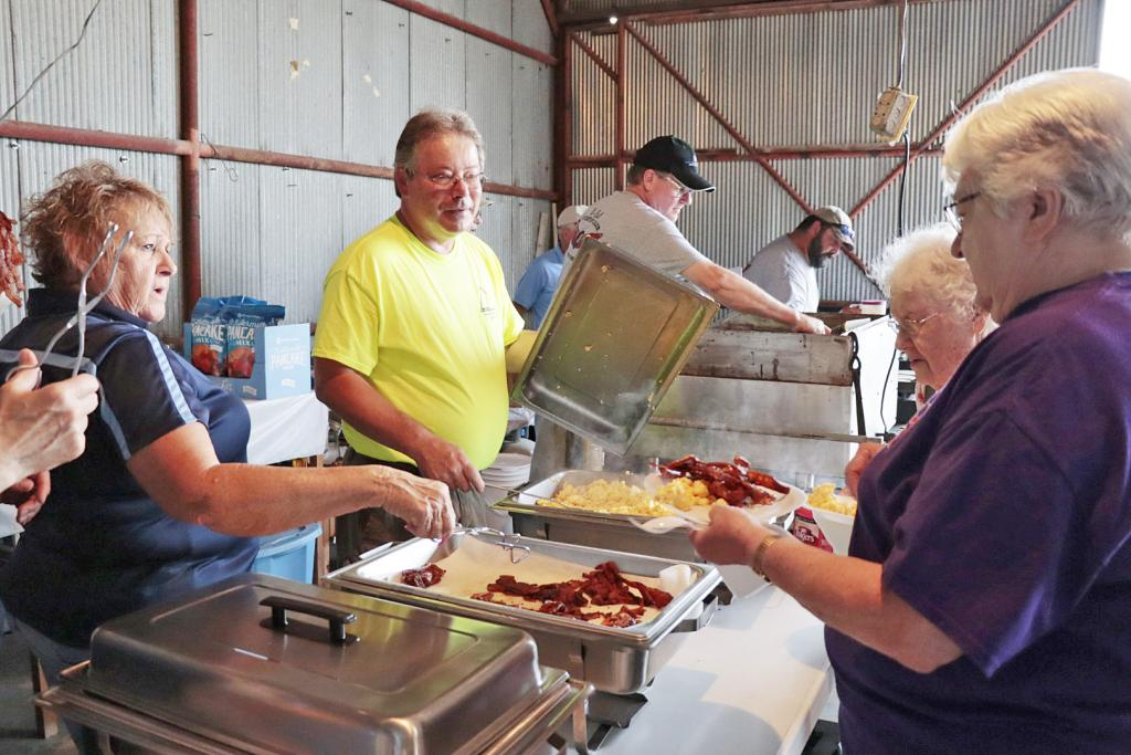Volunteers served bacon and eggs to two attendees at the 75th annual Flight Breakfast.
