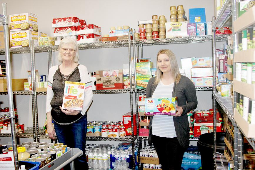 Rosie Thraen (left), outreach administrative assistant, and Dena Matthews, outreach director, are accepting donations to the food pantry.