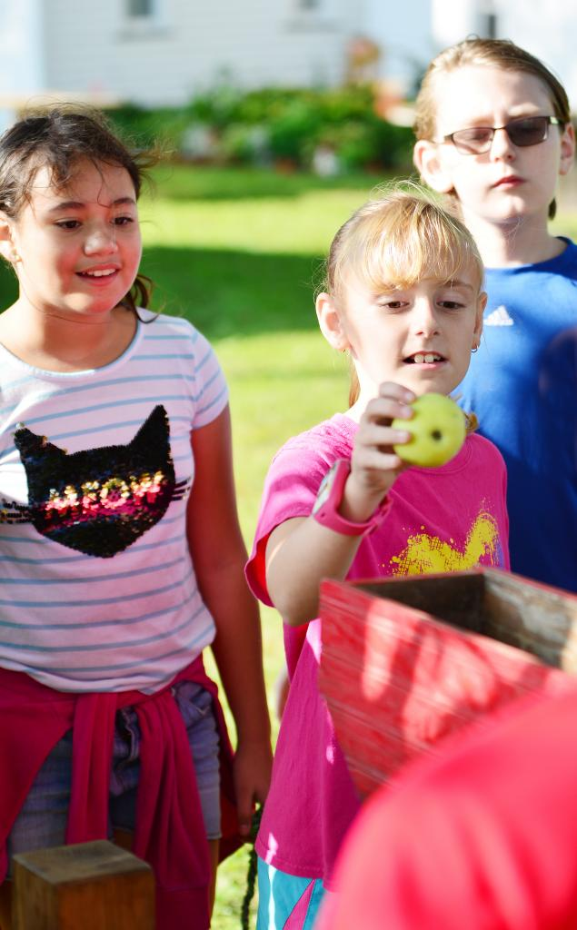 Ryelyn Summerfield tosses an apple into the apple press during youth day at the Greenridge Steam and Gas Show near Irwin last Friday.  Watching on are Maybelin Valladares Carballo and Evan Raveling.