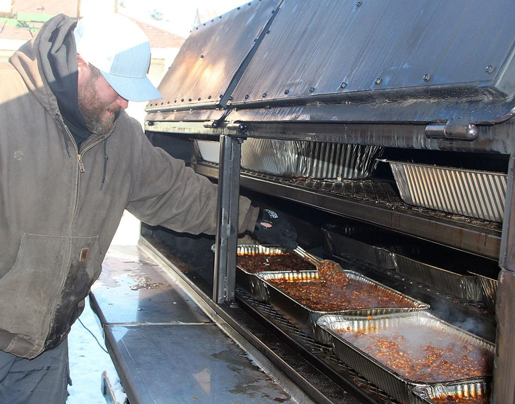 Kasey Bradley stirs the beans on the grill Saturday evening at the Shelby County Cattlemen's Association drive-through banquet.