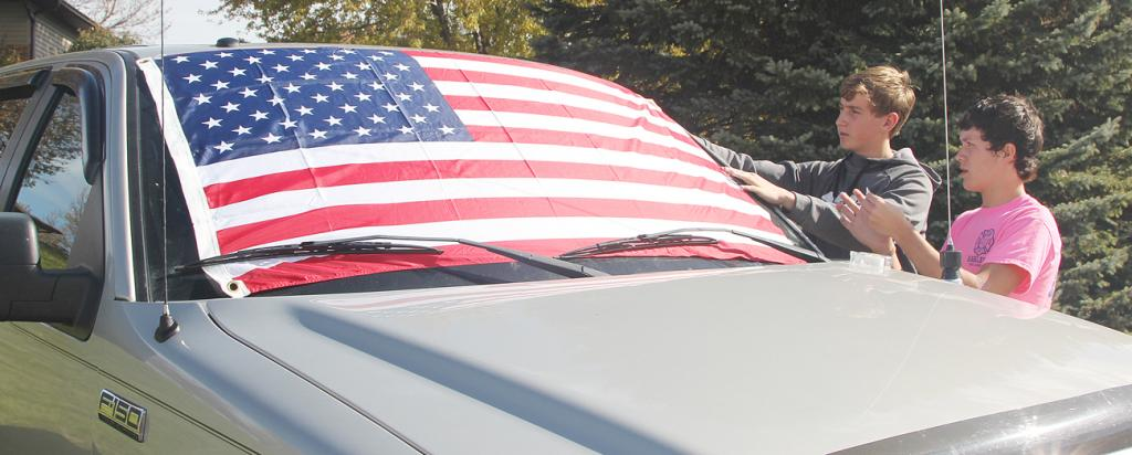 Cousins Wes Muenchrath (left) and Ben Muenchrath, both of Earling, show their support by draping a flag on the windshield of a truck parked in a yard on the road to the cemetery.