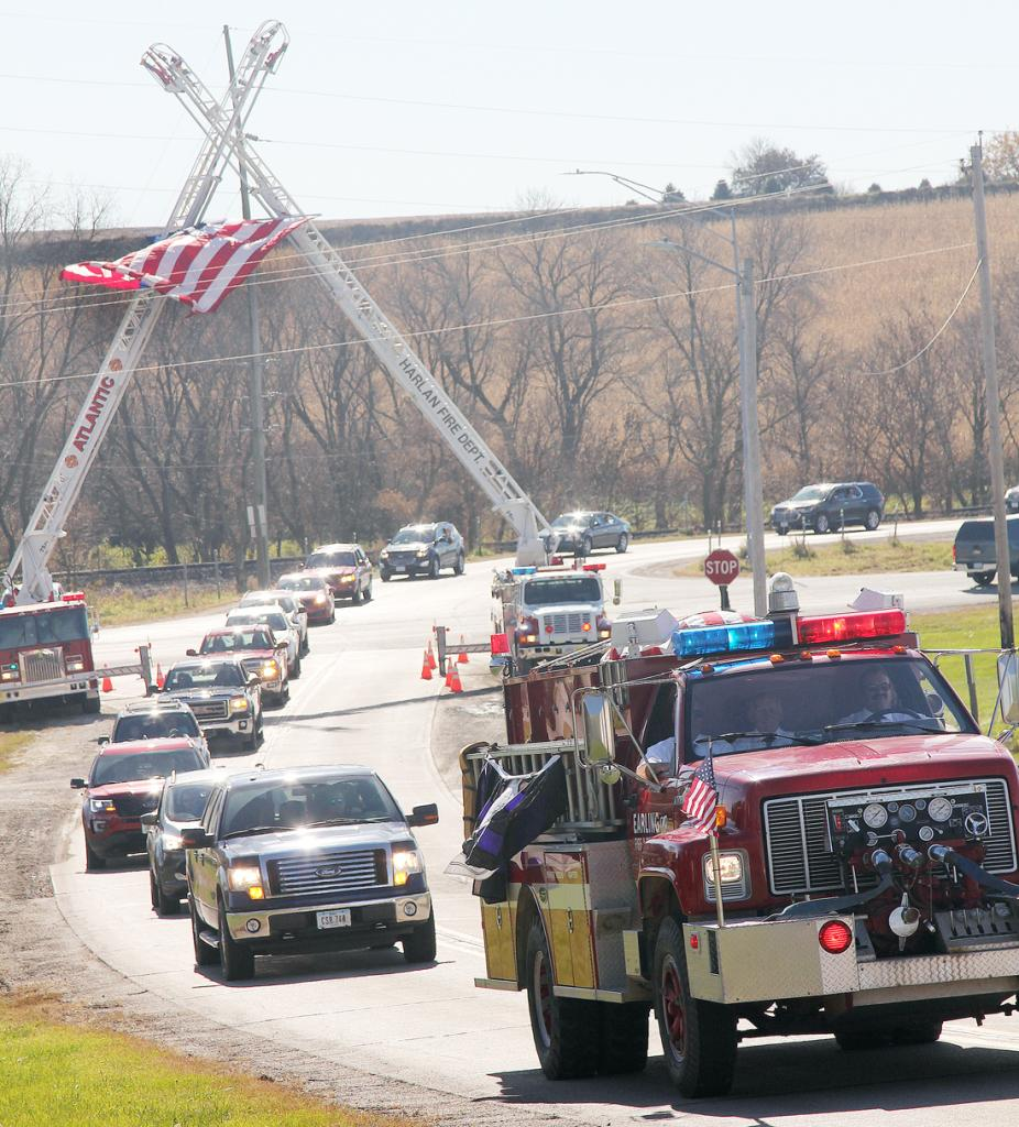 The processional heads to the cemetery underneath the American Flag.