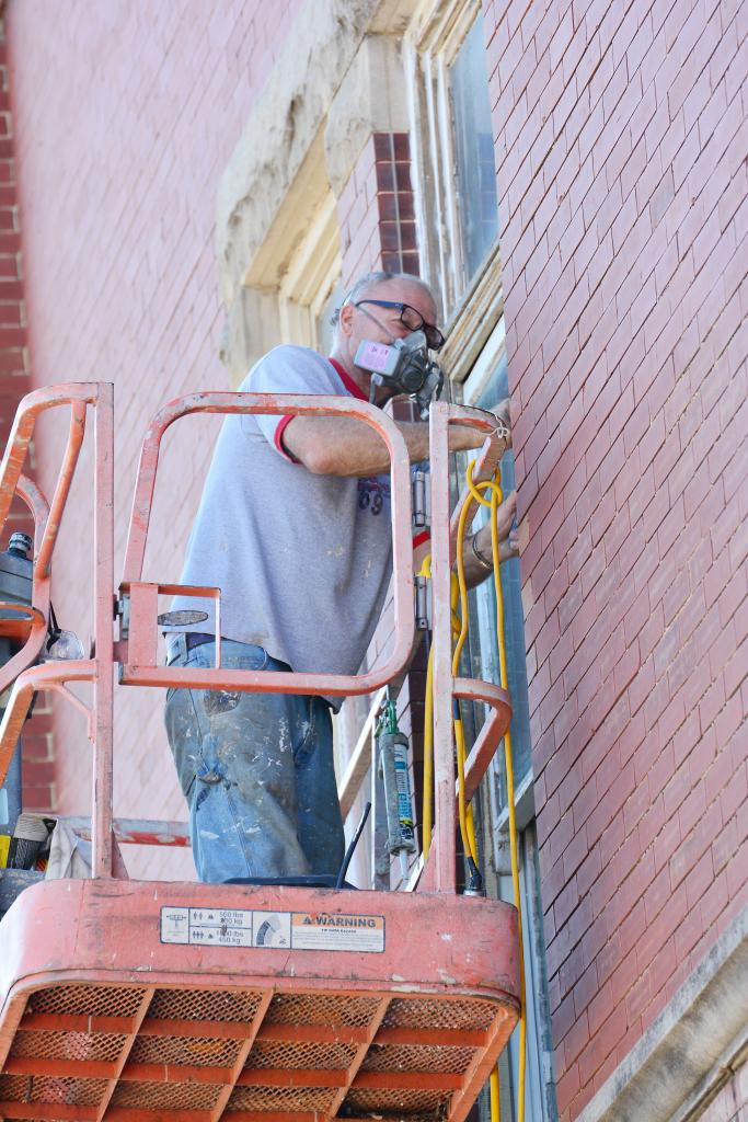 Jerry Henscheid works on the exterior windows of the building last fall.  Work is progressing substantially on the renovations.