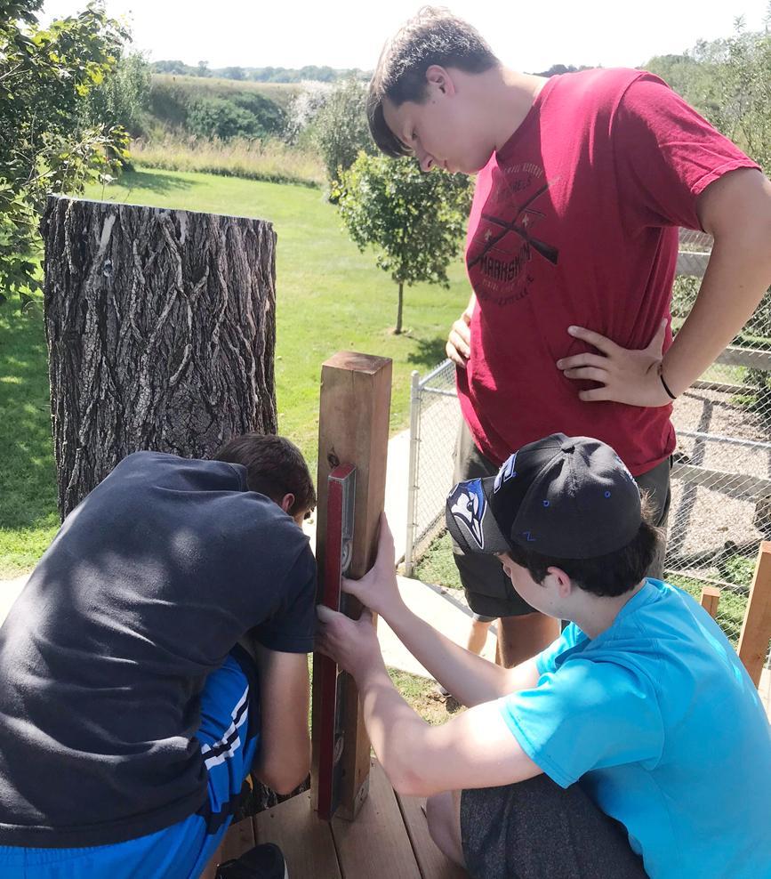 Klitgaard (standing) with volunteers Reece Nielsen and Logan Beeman working on the project this past summer.