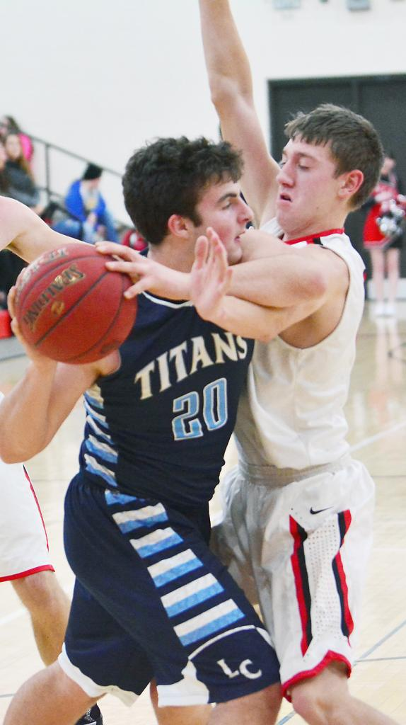 HCHS senior Ethan Knudson (right) clamps down on Lewis Central's Mitchell Brinkman Friday night.