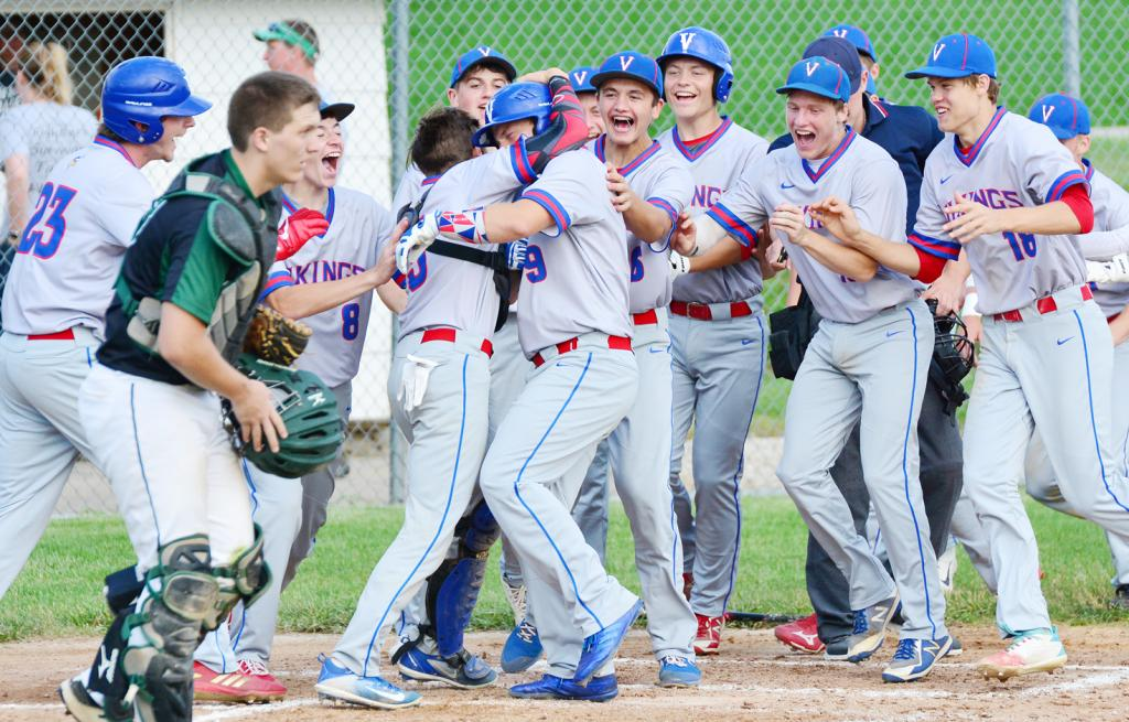 MILESTONE MOMENT -- AHSTW senior Gabe Madsen (9) is mobbed by his teammates at home plate after hitting his first career home run during the fifth inning of Friday's 14-1 victory at IKM-Manning. (Photos by Bob Bjoin)