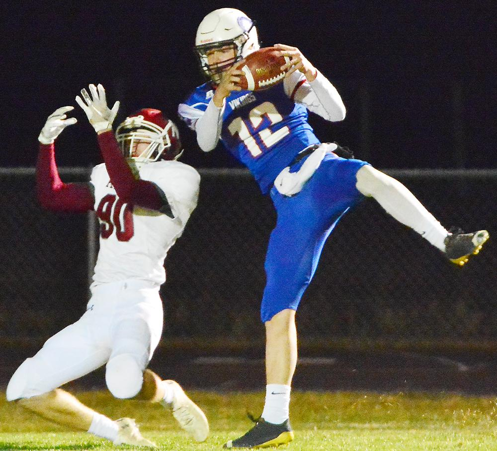 AHSTW senior Blake Osbahr (12) makes a leaping interception in front of a Newman Catholic receiver during Friday night's Class A quarterfinal playoff game. The Vikings picked off four Newman passes all told and advanced to the semifinal round at the UNI-Dome with a 31-14 victory.