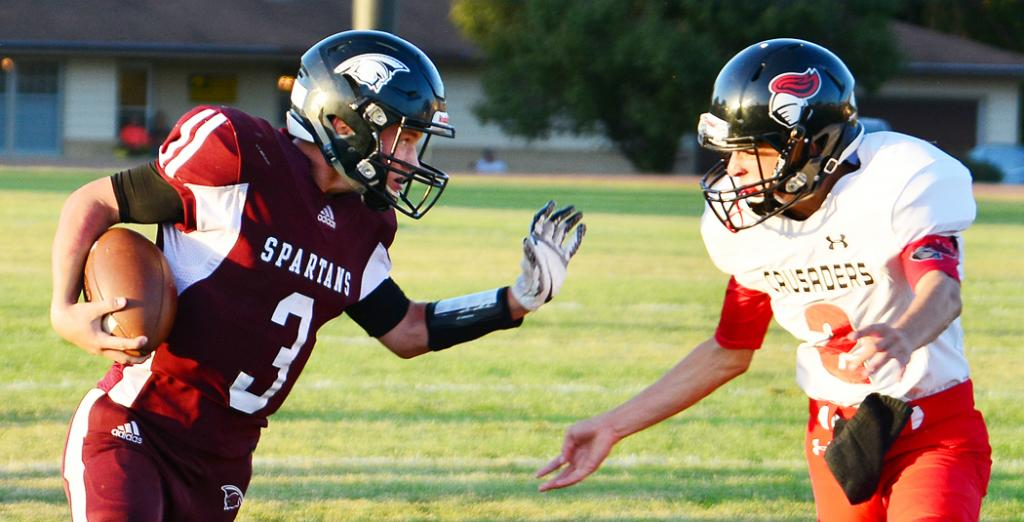 Spartan quarterback Trey Petersen (3) takes on the Crusaders' Easton Hays in the open field. (Photos by Bob Bjoin)