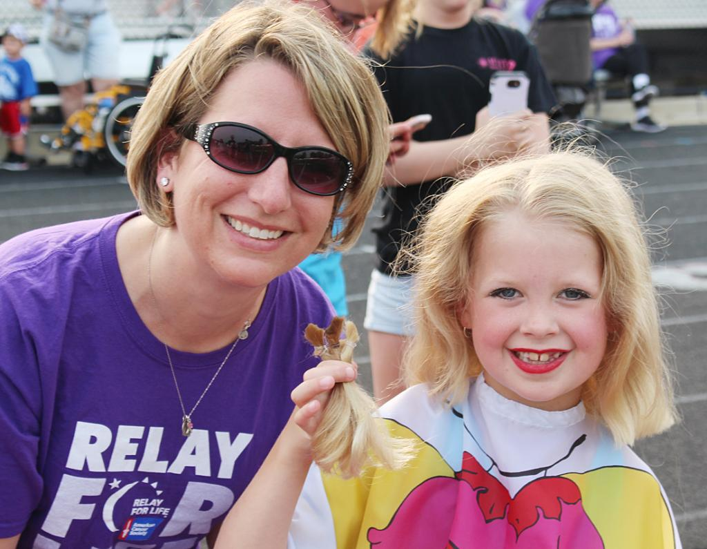 Sarah Strom, on the left, poses with her daughter, Hailey, who had her hair cut by her mother to be donated.  Participants at Relay for Life cut their hair to help bring awareness to cancer and to donate to cancer survivors.