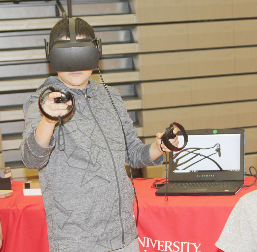 Edgar Mena participates in the virtual reality drawing program forward learning experience hosted by ISU Extension at the STEM event.