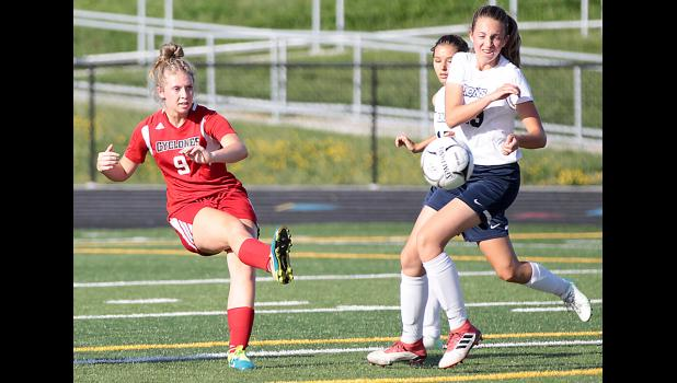 Harlan Community senior Alana Monson (9) clears the ball away from the Cyclone 18-yard box and two Des Moines Christian players during Friday's regional semifinal match.
