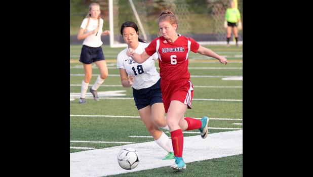 HCHS senior Jaden Anastasi (6) advances the ball up the sideline as Linette Leng pursues for the Lions.