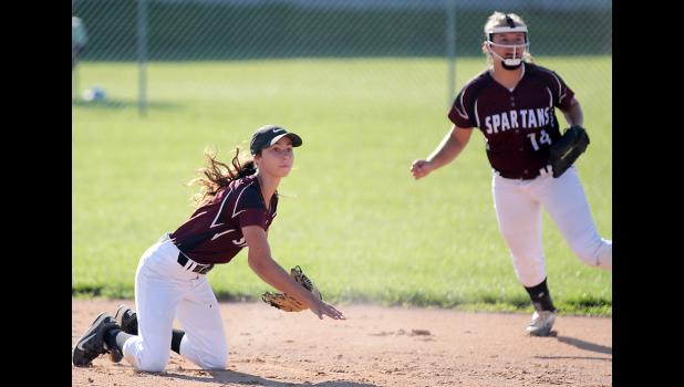 Exira-EHK second baseman Bailey Robertson (left) throws out a Southwest Valley runner at first after making a nice play up the middle. Shortstop Tatum Grubbs looks on.