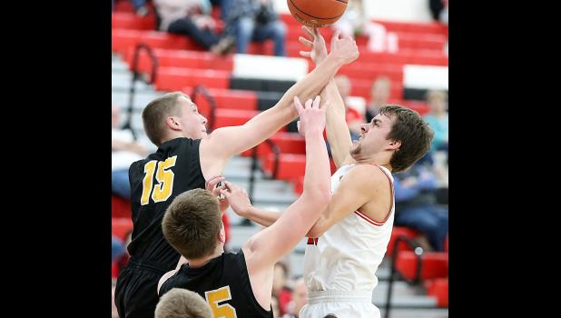 HCHS senior Brett Sears (right) draws a foul on Atlantic's Tyler Moen during Saturday's first half. Sears made 13-of-17 free throws and scored a career-high 31 points as the Cyclones defeated the Trojans 66-54. (Photos by Mike Oeffner)