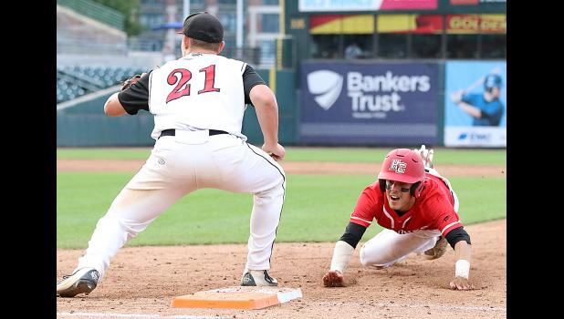 Cyclone junior Brett Sears dives back to first base safely as Davenport Assumption's Donovan Juarez (21) catches a pickoff attempt. (Photos by Mike Oeffner)