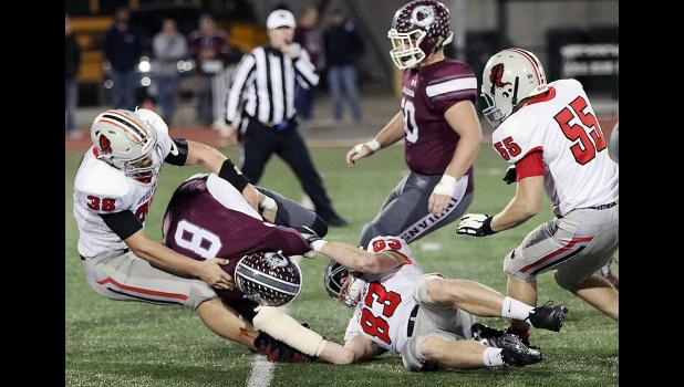 HCHS defensive linemen Caleb Bieker (38) and Jake McLaughlin (83) pull down Oskaloosa quarterback Cole Henry for a sack during Friday's playoff victory as Allen Fries (55) also rushes the passer.