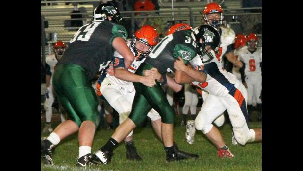 IKM-Manning's Nathan Blankman (30) fights for yardage against a pair of Manson-Northwest Webster tacklers Friday night. Blocking for the Wolves is Jacob Dentlinger.